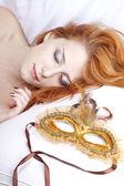 Sleeping woman near carnival mask. — Stock Photo