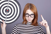 Angry red-haired girl with dartboard. — Stock Photo