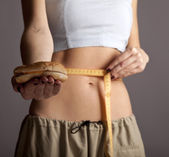 Beautiful and strong women's abs with metre nad burger. — Stock Photo
