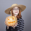 Royalty-Free Stock Photo: Funny girl in cap showing pumpkin.