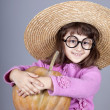 Funny girl in cap and glasses keeping pumpkin. — Stock Photo