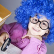 Funny blue-haired girl with loupe and books. — Stockfoto