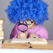 Stock Photo: Funny blue-haired girl with loupe and books.