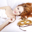 Woman in white lying in the bed near carnival mask. - Stock Photo
