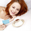 Woman in white lying in the bed near cup of coffee. — Stock Photo