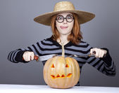 Funny girl in cap and fork with knife try to eat a pumpkin. — Стоковое фото