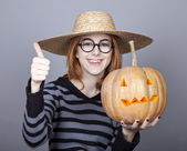 Funny girl in cap showing pumpkin. — Photo