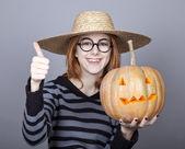 Funny girl in cap showing pumpkin. — Foto de Stock