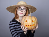 Funny girl in cap showing pumpkin. — Stock Photo