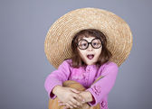 Funny girl in cap and glasses keeping pumpkin. — Foto de Stock