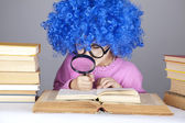 Funny blue-haired girl with loupe and books. — Stock Photo