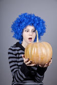Funny girl with blue hair keeping pumpkin. — Stock Photo