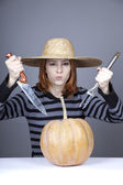 Funny girl in cap and fork with knife try to eat a pumpkin. — Photo