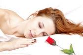 Rode roos in de buurt van vrij roodharige slapende vrouw — Stockfoto