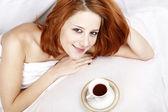 Femme en nuisette blanc couché dans le lit près de tasse de café — Photo