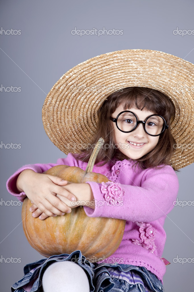 Funny girl in cap and glasses keeping pumpkin. Studio shot. — Stock Photo #4146877