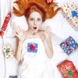 Surprised red-haired girl in bed with Christmas gifts. — Stock Photo