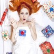 Surprised red-haired girl in bed with Christmas gifts. — Stock Photo #4299163