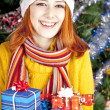 Funny girl in christmas cap with gift boxes — Stock Photo