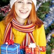 Royalty-Free Stock Photo: Funny girl in christmas cap with gift boxes