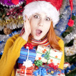 Funny girl in christmas cap with gift boxes — Stock fotografie