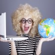 Stock Photo: Funny girl in glasses keeping notebook and globe.