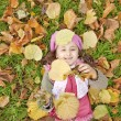 Lying down little girl at grass and leafs in the park. — Stock Photo