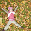 Lying down little girl at grass and leafs in the park. — Stock Photo #4336827