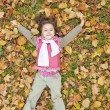 Stock Photo: Lying down little girl at grass and leafs in the park.