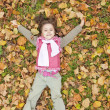 Lying down little girl at grass and leafs in the park. — Stock Photo #4336841