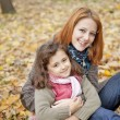 Two sisters sitting on the leafs in the park. — Stock Photo #4336891