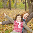 Two sisters sitting on the leafs in the park. — Stock Photo #4336919