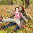 Two sisters sitting on the leafs in the park. — Stock Photo