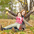 Two sisters sitting on the leafs in the park. — Stock Photo #4336936