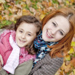 Stock Photo: Two sisters sitting on the leafs in the park.