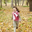 Cute running girl in autumn park. - Stock Photo