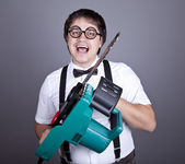 Men in suspender with bow tie and glasses keeping portable saw — Stock Photo