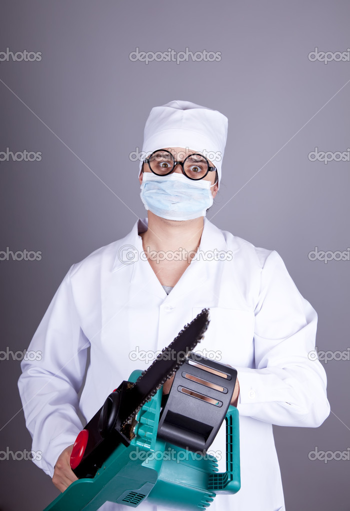 Crazy doctor with portable saw. Studio shot. — Stock Photo #4336956