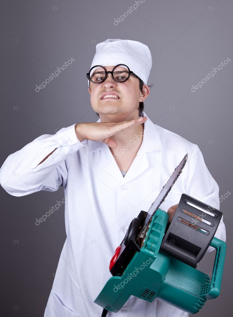 Crazy doctor with portable saw. Studio shot.  Stock Photo #4336972