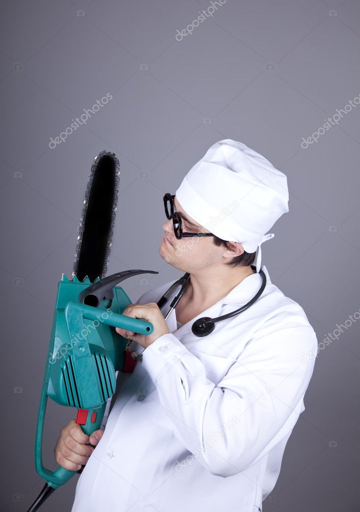 Crazy doctor with portable saw. Studio shot. — Stock Photo #4336979