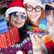 Two beautiful girls with gifts in christmas hats near christmas — Stock fotografie