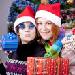 Two beautiful girls with gifts in christmas hats near christmas — Stock Photo #4356681