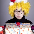 Funny girl in glasses with christmas gifts. - Stock Photo