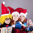 Three girlfriends in funny hats with christmas gifts. — Stock Photo #4356786