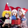 Three girlfriends in funny hats with christmas gifts. — Stock Photo #4356789