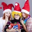 Three girlfriends in funny hats with christmas gifts. — Stock Photo
