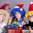 Three girlfriends in funny hats with christmas gifts. — Stock Photo #4356814