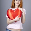 Beautiful red-haired girl with toy heart. — Stock Photo