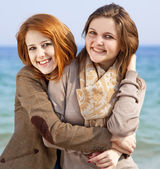 Two happy girls at spring beach. — Stock Photo