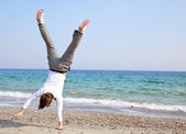 Young guy dances a break-dans on a beach — Stock Photo